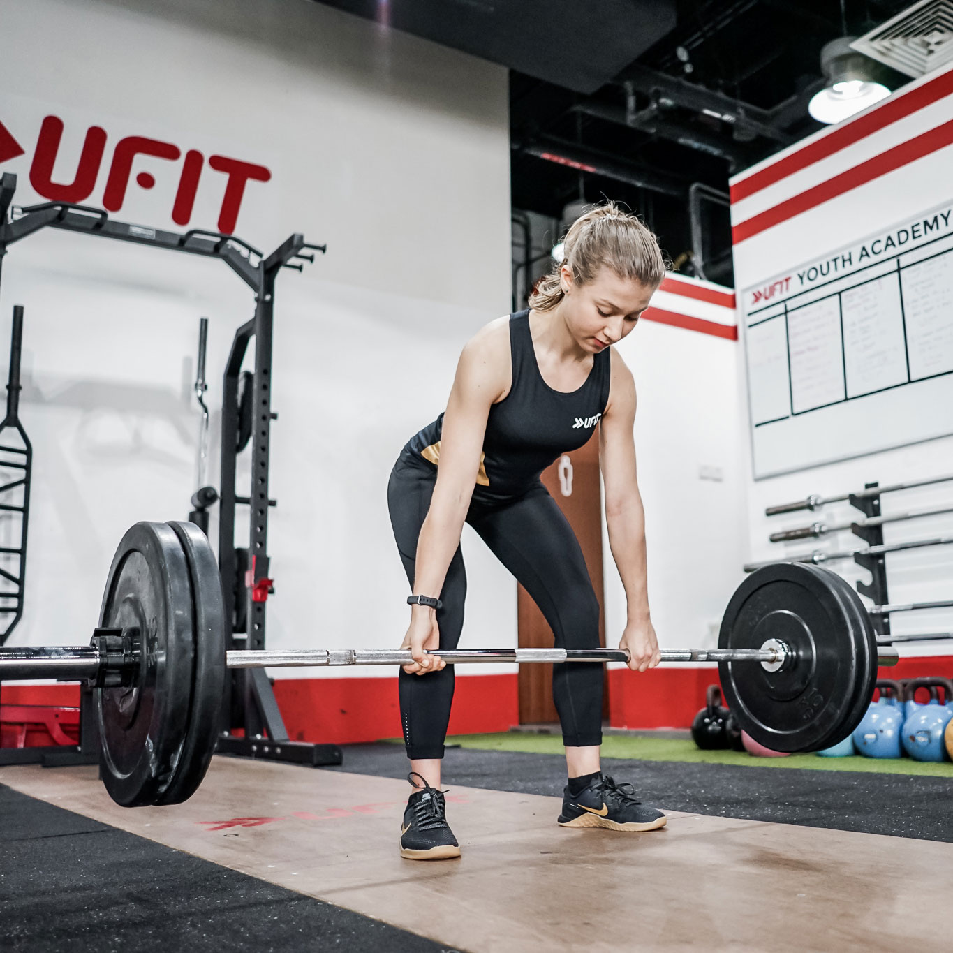 Female trainee performing conventional deadlift