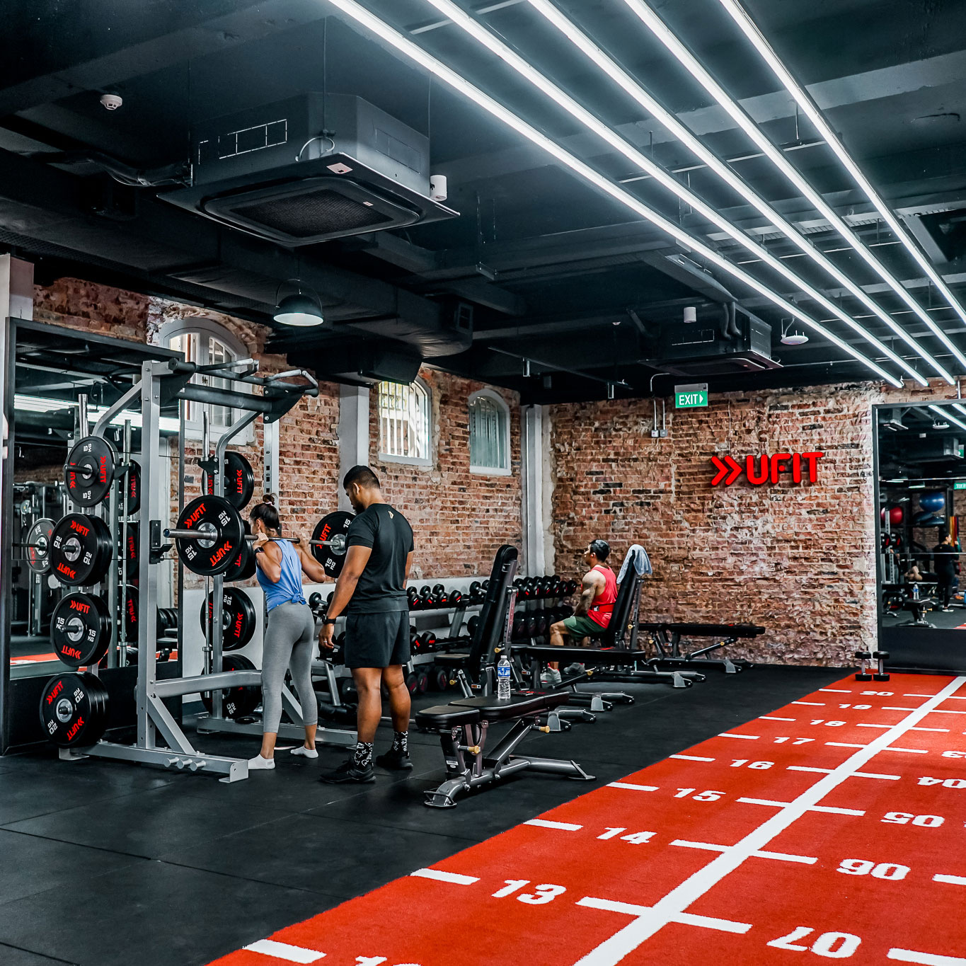 Personal trainer with woman squatting at power rack